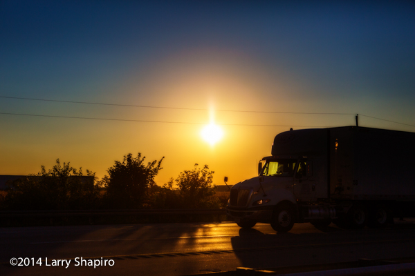 sunset with truck silhouette on the highway