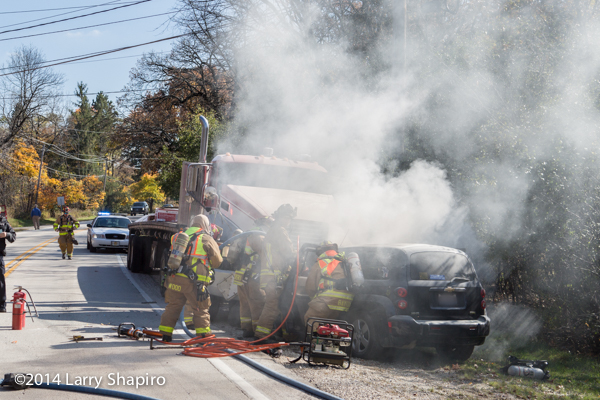 firemen battle car fire with trapped driver