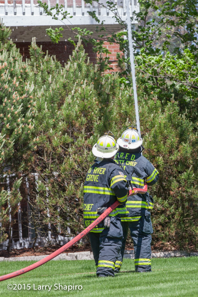 firemen at a fire scene operating a hose line