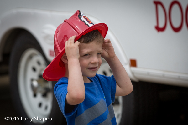 young boy wearing a fire helmet