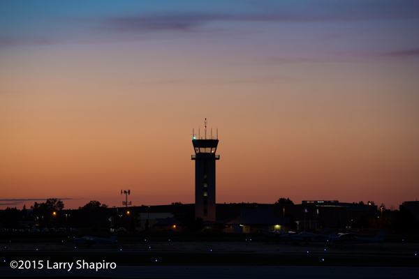airport control tower silhouetted at sunset