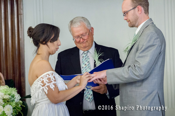 bride placing a ring on the groom