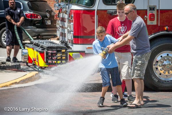 Boys get a chance to use a fire hose