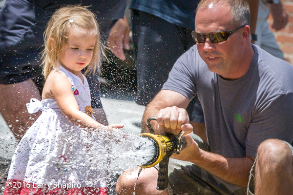 Fire chief and small girl with fire hose.
