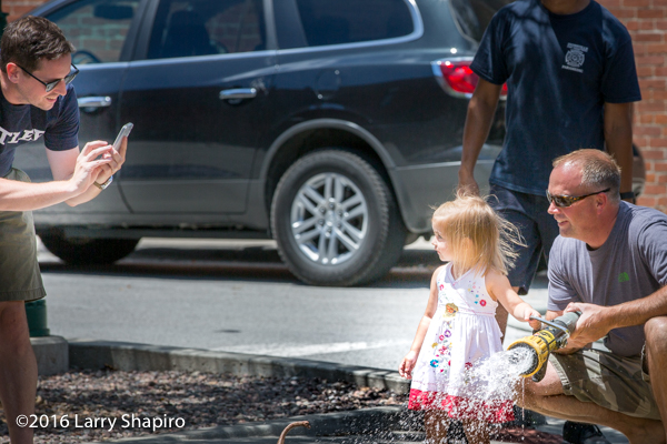 Father taking a picture of his daughter with a fire hose