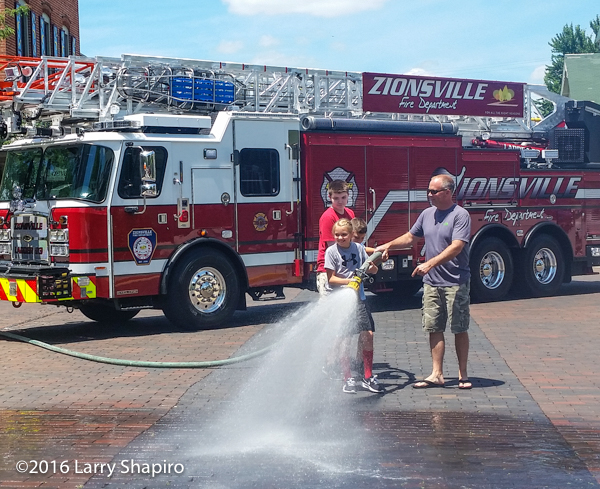 brother and sister help with fire hose