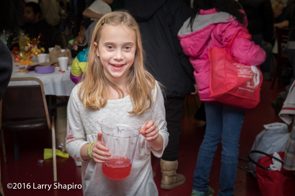 young girls serving fruit punch to the homeless