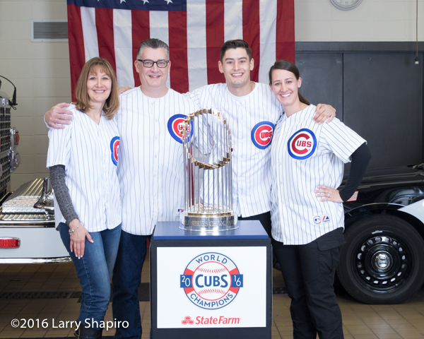 Cub fans posing with the world series championship trophy