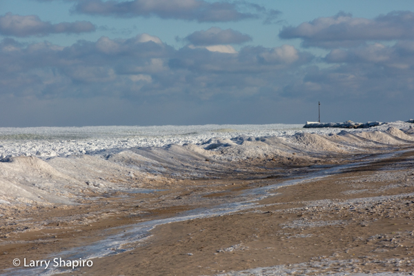 waves crashing on the beach covered with ice and snow