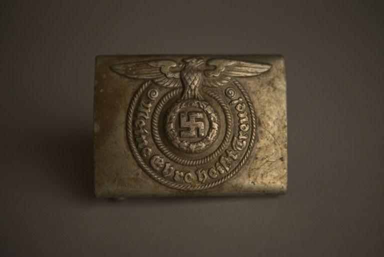 Hebilla metálica de cinturón de las SS nazis, colección del Museo Estatal de Auschwitz-Birkenau Foto por Pawel Sawicki © Auschwitz-Birkenau State Museum - Musealia