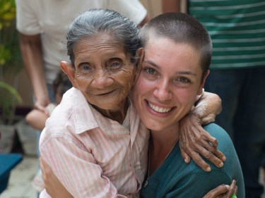 A smiling young woman and a petite smiling elderly woman are hugging each other in a warm contact embrace.