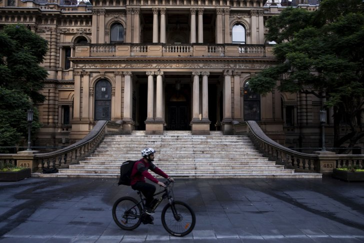 Food delivery rider in red top and white helmet rides past Sydney Town Hall.