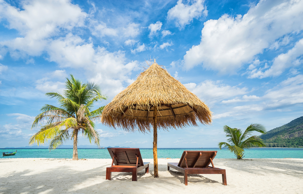 Lounge chairs beneath a thatched umbrella on a tropical beach