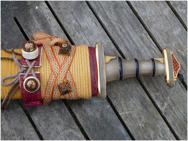 Parte superiore della spada inguainata, il manico, la base del pomello e la parte centrale della guardia sono in corno di bovino