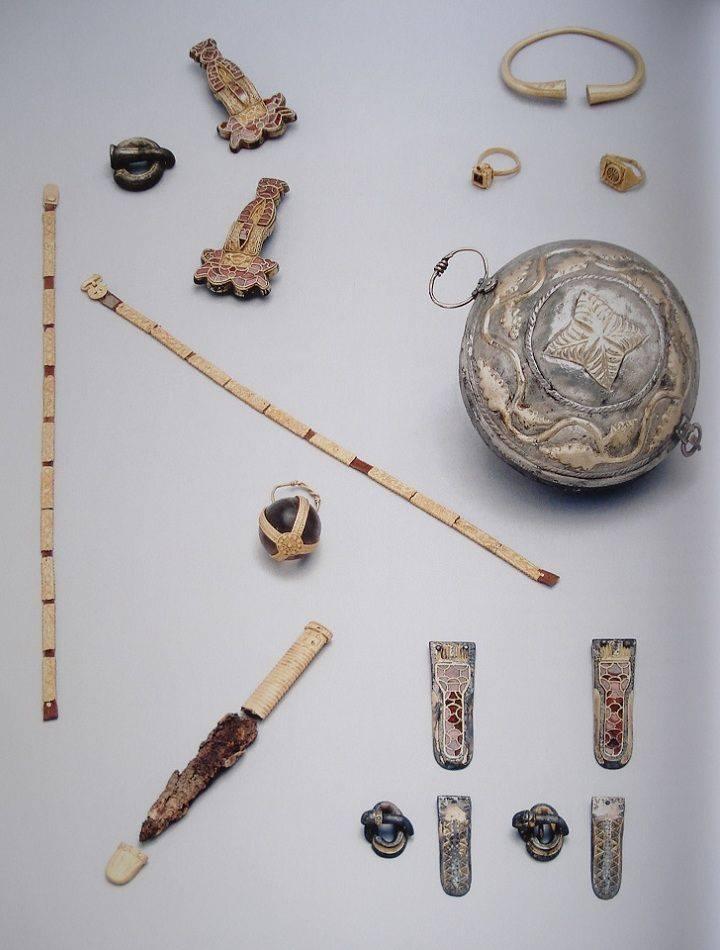 Bulla in argento e argento dorato, lacci per calze ornati da placchette in osso con fibbie e puntali cloisonné, armilla e anelli in oro, coltellino con manico e puntale di fodero in osso