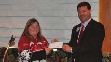 President Dave presents check to Barbara of New Horizons.