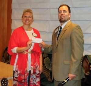 Jaime Goldsmith presented President Michael with a check towards our food can drive.
