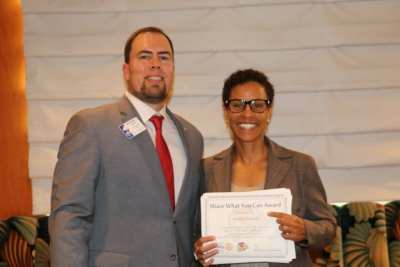 President Michael presents our speaker Joselyn Counsins of the Federal Reserve Bank with a Share What You Can Award.