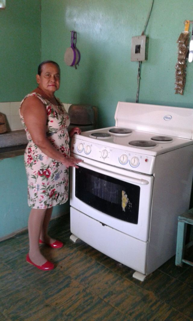 Gloria and a precious commodity, her gas stove; a luxury in the village.