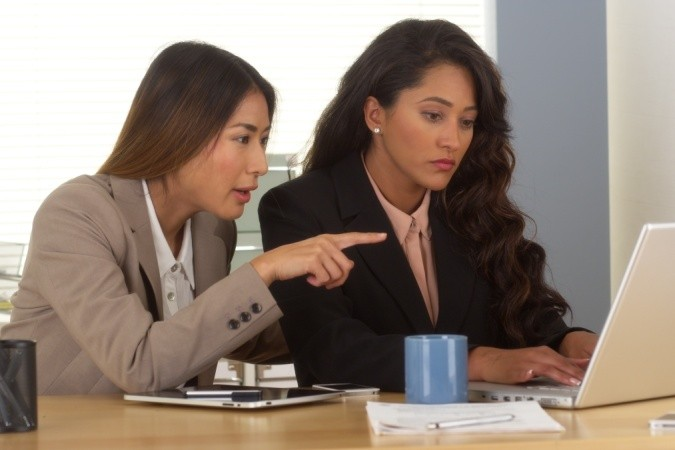 Multi-ethnic businesswomen working on laptop