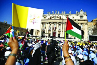 A member of the faithful wave Palestinian flag and Vatican flag before Pope Francis leads a ceremony for the canonisation of four nuns at Saint Peter's square in the Vatican City, May 17, 2015. The four nuns being canonised include two Palestininan nuns, Marie Alphonsine Ghattas, founder of the first Catholic congregation in Palestine, and Mariam Baouardy Haddad, who established a Carmelite convent in Bethlehem. REUTERS/Tony Gentile - RTX1DAL4