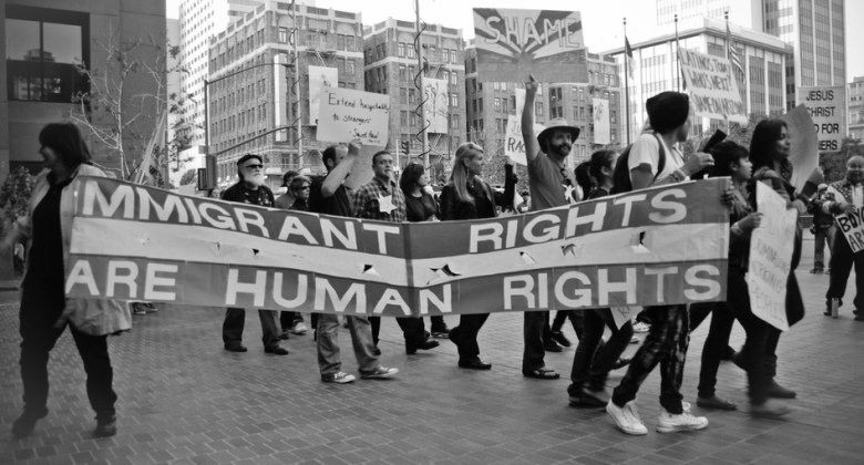 marchers carrying banner that reads immigrant rights are human rights