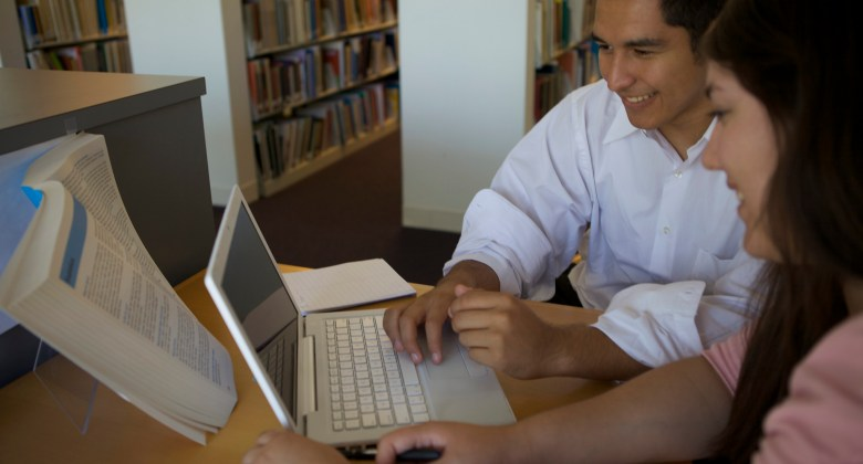 two latino students smiling as they read something on laptop screen in library