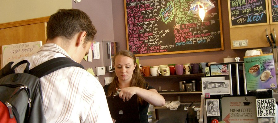 Coffee shop cashier behind the register at a coffee shop accepting payment from a customer wearing a backpack