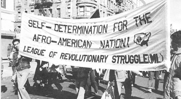 """Black and white photo of activists holding a banner that reads """"Self-Determination for the Afro-American Nation! League of Revolutionary Struggle (ML)"""""""