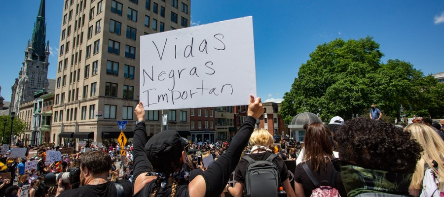 "Crowd in a large urban city center with a protestor holding a sign reading ""vidas negras importan"""