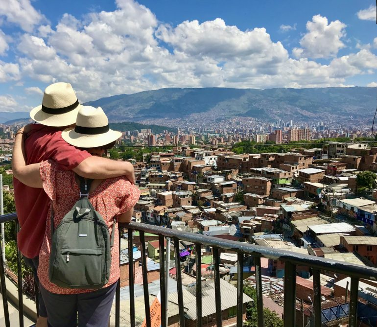 Two people in Panama hats looking at a panoramic view of Medellin, Colombia