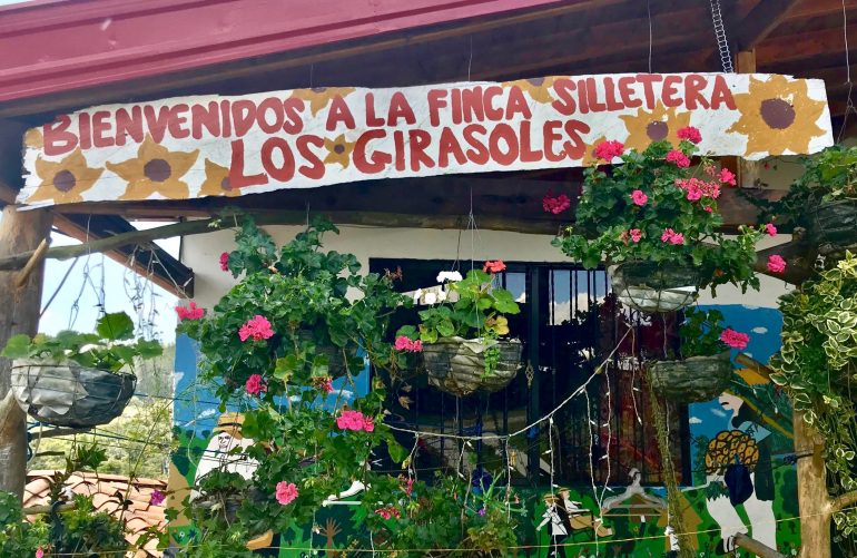 sign with flowers welcoming visitors to the Finca Los Girasoles flower finca