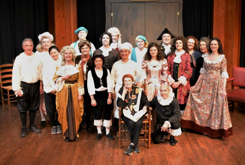 Cast photo 2019 - actors in costume along with crew standing on stage at the George Ignatieff Theatre, surrounding artistic director Paulette Collet