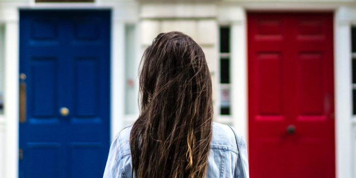 Girl standing in front of three doors (blue, white, and red)