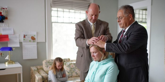 A woman getting a priesthood blessing
