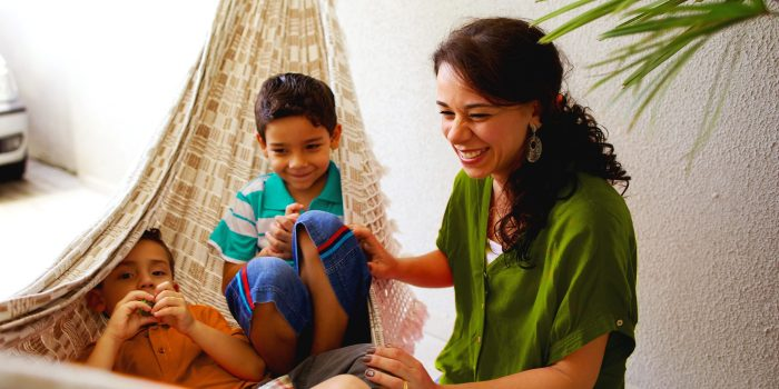 A mother laughs and plays with her children, who are sitting in a hammock.