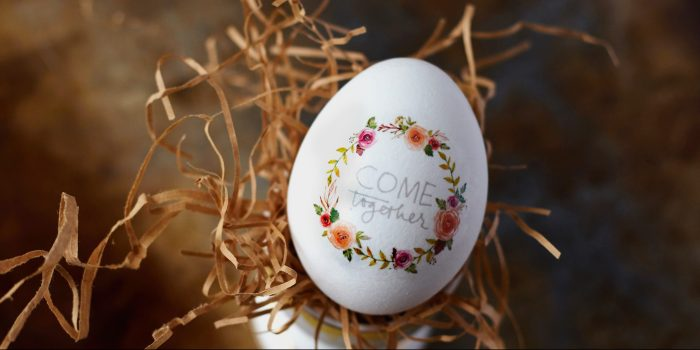 """An egg with the words """"Come Together"""" and a wreath of flowers painted on it."""