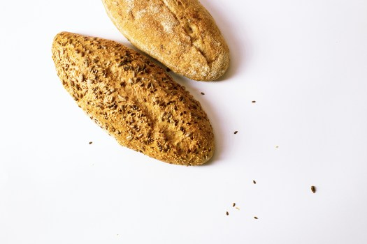 Two loaves of bread sit on a white background.