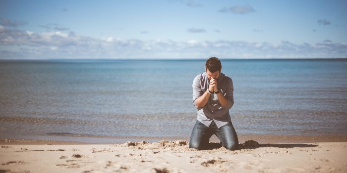 Man kneeling on a beach in fervent prayer