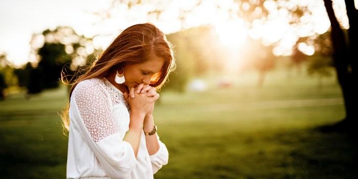 Woman praying beside tree