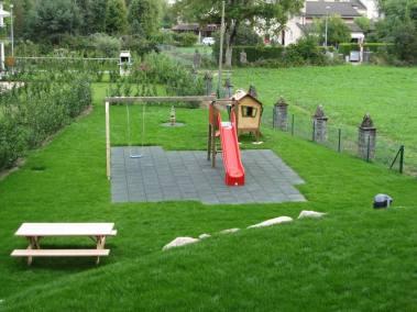 Un combiné balançoire et toboggan avec des tables de jardin aménagé pour un bâtiment, réalisation Lattion & Veillard paysagiste dans le Valais