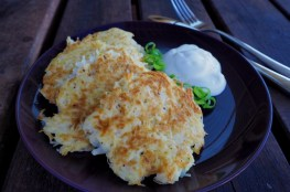 Potato pancakes on a dark plate with green onion and sour cream