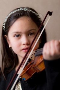 A girl gazes pensively into the lens of photographer Heather Tristan as she plays her violin. Laughing Magpies Photography has captured yet another poignant moment at a violin recital for children in their classic and elegant portrait style.