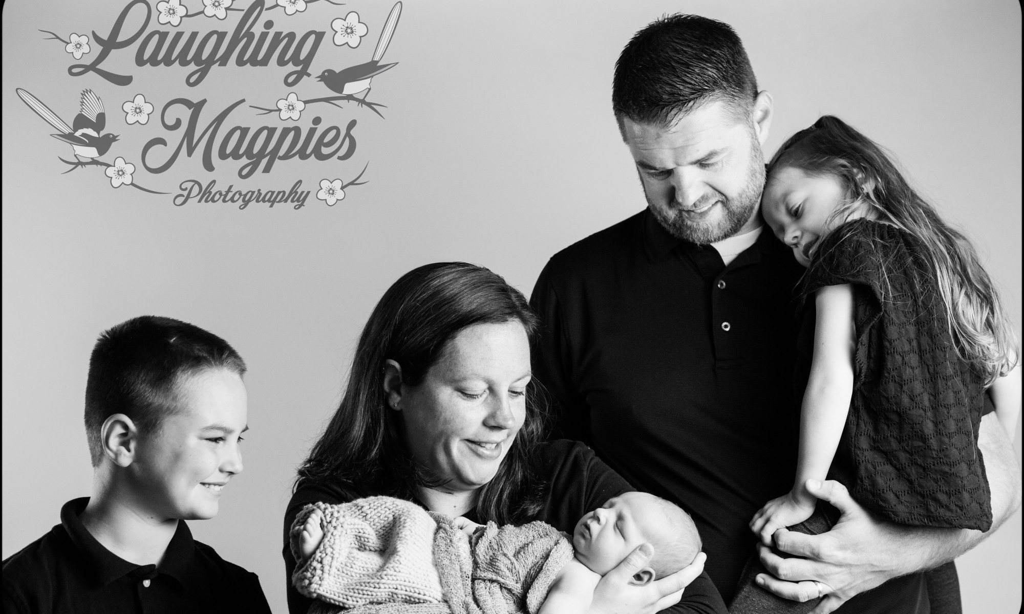 A Smiling family gathers around their precious newborn baby boy to welcome him into the family. Photographed by Heather Tristan of Laughing Magpies Photography in Greater Seattle, Washington