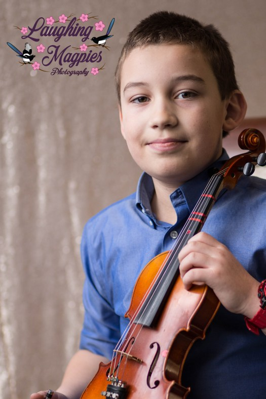 Heather Tristan of Laughing Magpies Photography in Bothell, Washington captures a young boy proudly displaying his violin during a winter violin recital portrait session in Lynnwood, Washington.