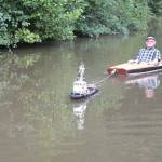 A Tiny Remote Controlled Tugboat Tows a Man in a Kayak Along a Canal in the English West Midlands