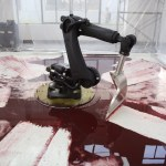 A Large Robotic Arm Futilely Tries to Clean a Blood Red Mess in the Art Installation 'Can't Help Myself'