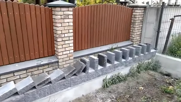 A Man Building Wall Sets Up Row Of Stone Slabs That Almost All Fall Into Place Like Dominoes