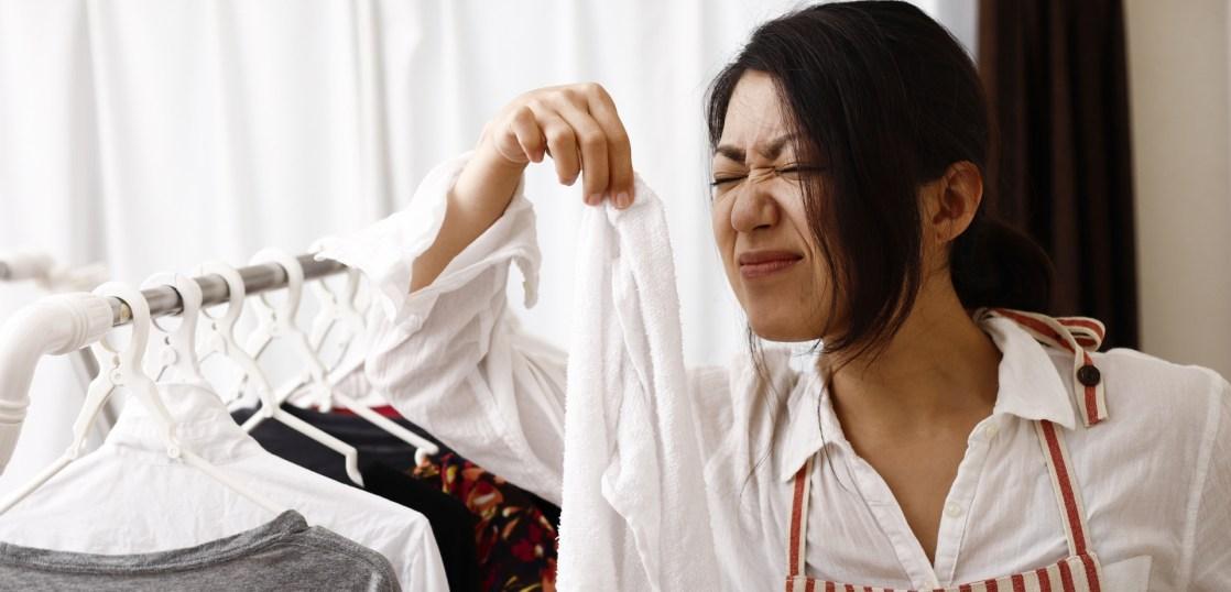 タオルが臭いので顔をしかめる主婦