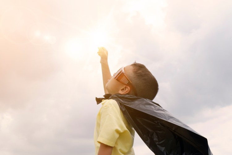 a small boy wearing a superhero costume raises his arm toward the sky, looking toward the sun. He is wearing a yellow shirt, red glasses, and a black cape.